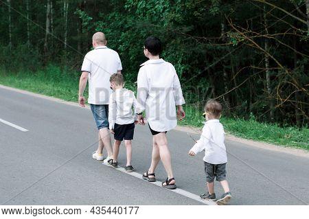 A Family Follow Each Other On The Asphalt Lane