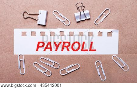 On A Brown Background, White Paper Clips And A Torn Strip Of White Paper With The Text Payroll