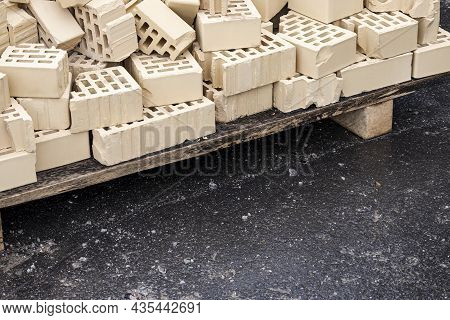 A Wooden Pallet With The Remains Of A Light Brick Stands On Wet Asphalt After Construction With Copy