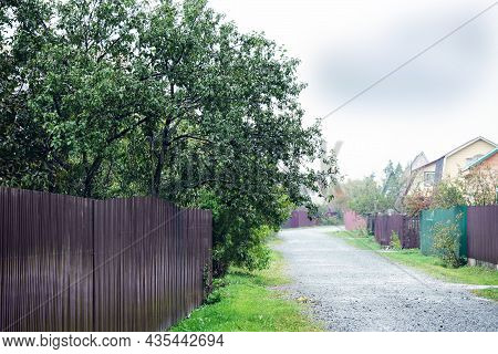 Rural Road Goes Along Fences Of Private Houses. Simple Rural Background, Private Sector, Village Con