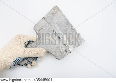 A Hand Of A Constructor, Builder, Plasterer Holding Dirty Used Spatula, Trowel Against White Backgro