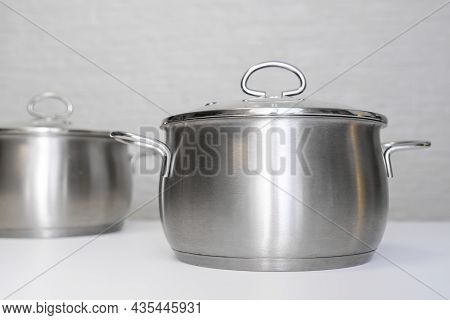 Stainless Steel Pots, Stockpots On White Table, Eco Friendly Kitchen Utensils Without Harm, Harmless