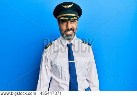 Middle age man with beard and grey hair wearing airplane pilot uniform winking looking at the camera with sexy expression, cheerful and happy face.