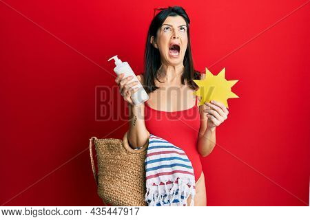 Young hispanic woman wearing swimsuit, holding sunscreen lotion and sun paper angry and mad screaming frustrated and furious, shouting with anger looking up.