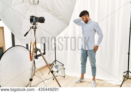 Arab young man posing as model at photography studio suffering of neck ache injury, touching neck with hand, muscular pain