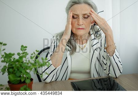 Tired Senior Grey Haired Businesswoman In Striped Jacket With Eyeglasses Is Working In Her Office Si