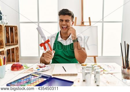 Young hispanic man at art studio holding degree winking looking at the camera with sexy expression, cheerful and happy face.