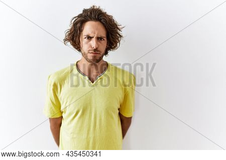 Young hispanic man standing over isolated background skeptic and nervous, frowning upset because of problem. negative person.