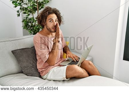 Young hispanic man sitting on the sofa at home using laptop hand on mouth telling secret rumor, whispering malicious talk conversation