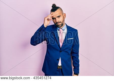 Young hispanic man wearing business suit and tie worried and stressed about a problem with hand on forehead, nervous and anxious for crisis