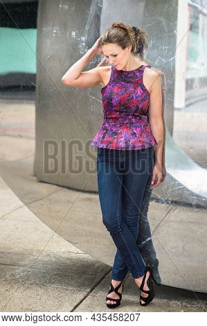 Dressing In A Purple Pattern Top And Blue Jeans, A Young Pretty Woman Is Standing By A Mirror Wall A