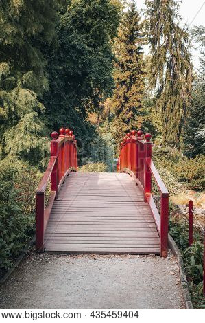 Red Wooden Bridge In A Park. Beautiful Nature.