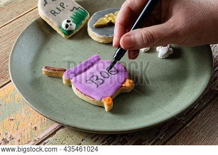 Confectioner Writing On A Purple Cauldron-shaped Buttery Biscuit.