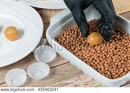 Confectioner Placing The Brigadeiro (brigadier) Of Dulce De Leche On Salty Crunchy Caramels.