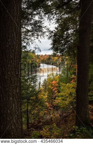 Beautiful Autumn Photograph Of Upper Tahquamenon Falls In Michigan With Water Cascading Into The Riv