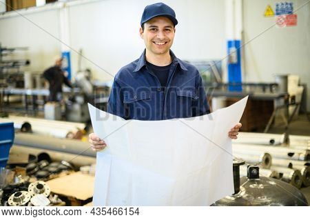 One engineers looking at a blueprint in a facility