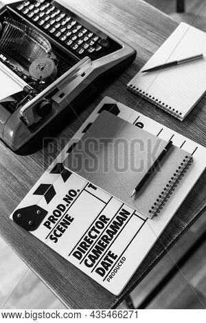 Clapper board and vintage typewriter at wooden desk table. Writer or screenwriter creative concept