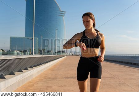 Fit Sportswoman In Sports Bra And Shorts Running And Checking Pulse On Smart Band During Cardio Work