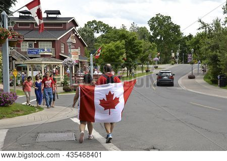 Unionville, Ontario / Canada - July 01, 2014: Couple Holding Flag At On The Canada Day Parade