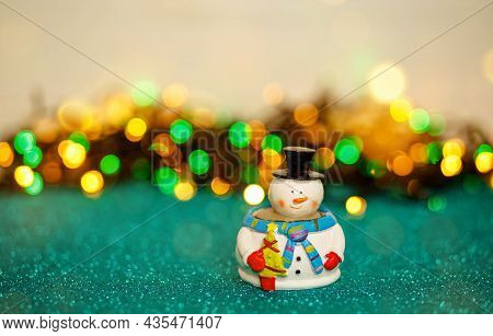 Christmas Snowmen Decoration. Small Snowman Toy In Front Of Defocused Xmas Lights. Holiday Card. Chr