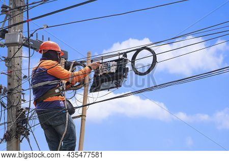 Low Angle View Of Technician On Wooden Ladder Is Installing Fiber Optic System In Internet Splitter