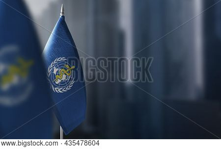Small Flags Of World Health Organization Who On A Blurry Background Of The City