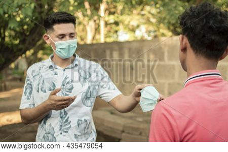 Young Man Sharing Mask To Another Young Man, Young Man Giving A Mask To Another Young Man, Concept O