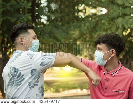 Two Young People Bumping Their Elbows, Image Of Two Young People Bumping Their Elbows In A Friendly