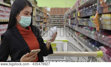 Young Smart Business Asian Woman Shopper With Face Mask Choosing Grocery To Buy From Shelf In Superm
