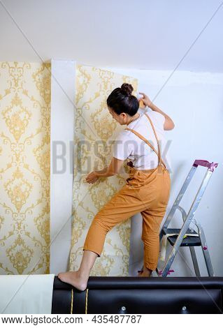 Asian Woman Applying New Wallpaper At Home. Renovate And House Decoration.