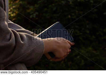 Young Unrecognizable Caucasian Woman Holding Old Vintage Book. Autumn In Park. Autumn Romantic Mood,