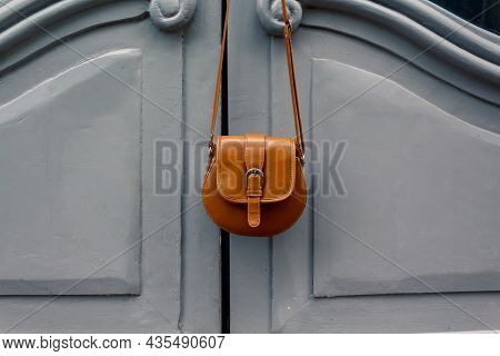 Forgotten Things. Womans Bag Hanging On Door. Vintage Style. Small Brown Bag On Amazing Blue Doors.