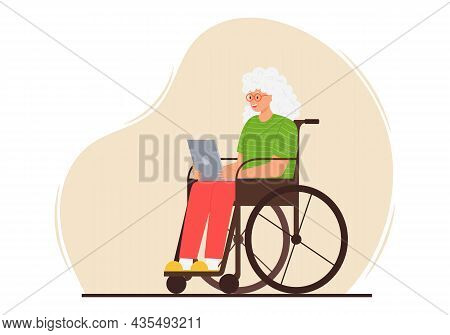 A Happy Elderly Woman Is Sitting With A Laptop In A Wheelchair . A Smiling Adult Grandmother With Gr