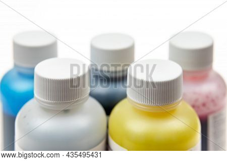 Five Plastic Bottles With Different Inks For Ink-jet Printer On A Light Background