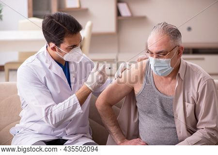 Young male doctor visiting old patient in vaccination concept