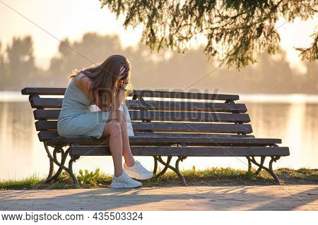 Lonely Sad Woman Sitting Alone On Lake Shore Bench On Warm Summer Evening. Solitude And Relaxing In