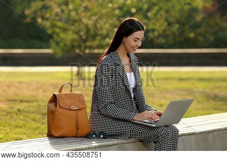 Beautiful Young Woman With Stylish Backpack And Laptop On Bench In Park