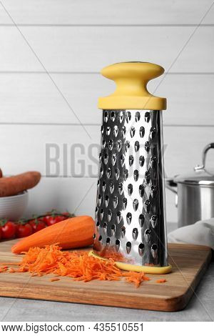 Grater And Fresh Ripe Carrot On Table