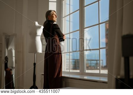 European senior woman with grey hair posing by window and dummy indoors
