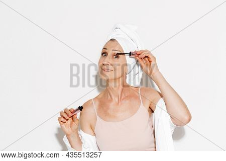 Senior woman wrapped in towel applying mascara while doing makeup isolated over white wall