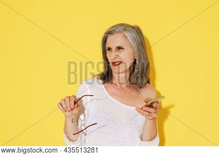 Mature woman in eyeglasses grimacing while using mobile phone isolated over yellow wall
