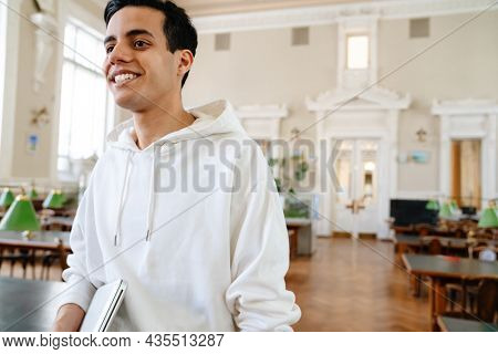 Young middle eastern student man holding laptop and smiling in library