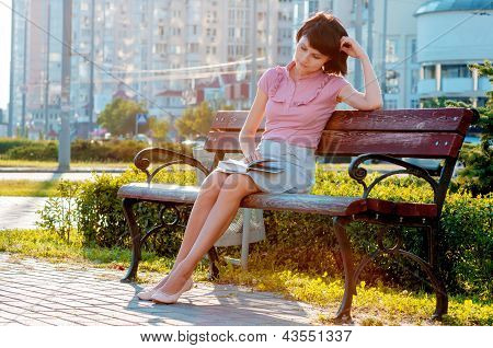 Beautiful woman reading book on bench
