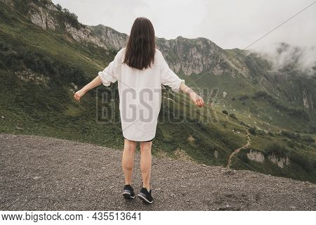 The Girl Enjoys The Beauty And Majesty Of The Mountains. A Man In A White Shirt Stands With His Back