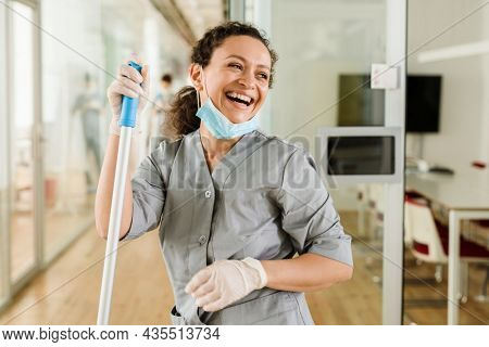 Middle eastern cleaning woman smiling while standing with mop indoors