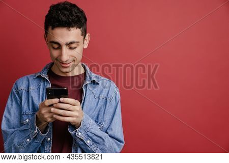 Young middle eastern man smiling and using mobile phone isolated over red background