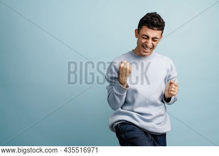 Young middle eastern man screaming while making winner gesture isolated over blue background