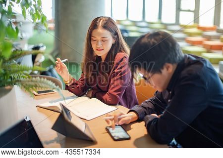 Business Meeting And Partnership Concept. Attractive Asian Businesswoman Talking To Colleagues About