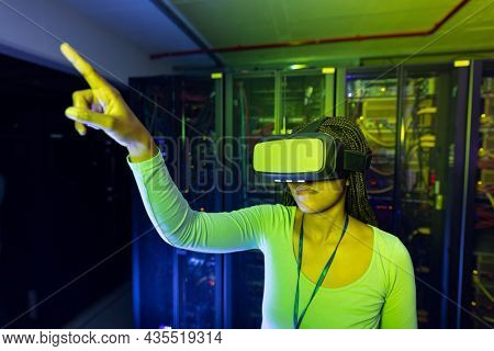 African american female computer technician wearing vr headset and working in server room. digital information storage and communication network technology.