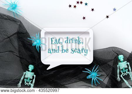 Halloween Flat Lay With Hands And Spiders. Text Eat, Drink And Be Scary In White Frame. Skeletons In